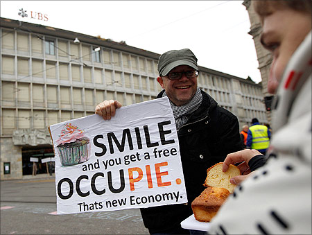 A demonstrator offers cakes as he attends Occupy Paradeplatz protest in front of Swiss banks UBS and Credit Suisse in Zurich.