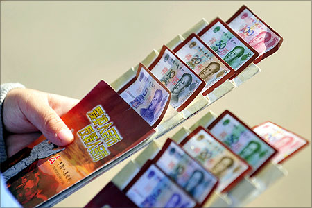A resident looks at a brochure of yuan banknotes at a branch of People's Bank of China.