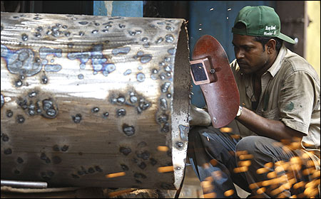 A worker uses a welding machine at a metal workshop in Mumbai.