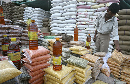 A vendor arranges packets of pulses at a wholesale market.
