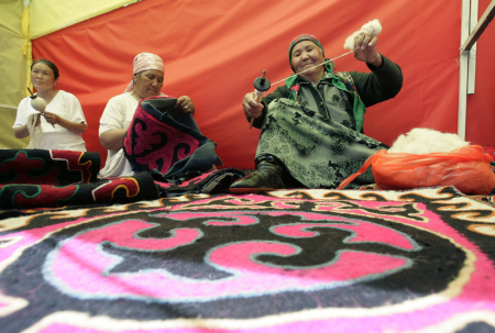 Women spin yarn at a presentation of traditional handicraft in Osh.