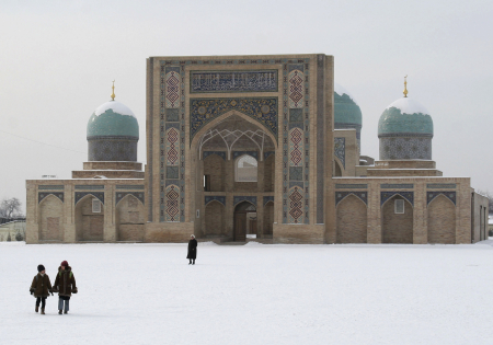 People walk across a snow covered Khast Imam square in Tashkent.