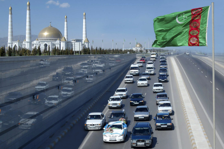 A wedding convoy passes Turkmen flag near mausoleum of the country's former leader Niyazov near Ashgabat.