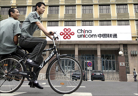 Security guards ride past a China Unicom office in Beijing.