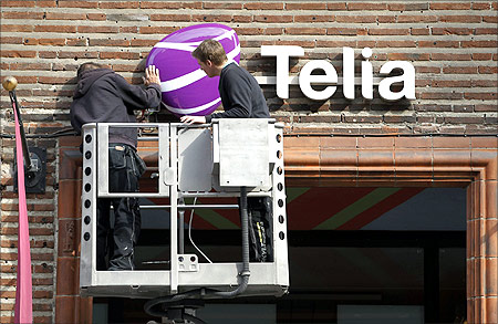 Workmen install a sign with TeliaSonera's new corporate logo.