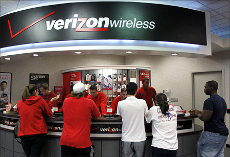 Customers purchase the iPhone 4 shortly after the phone went on sale with the Verizon Wireless network in Boca Raton.