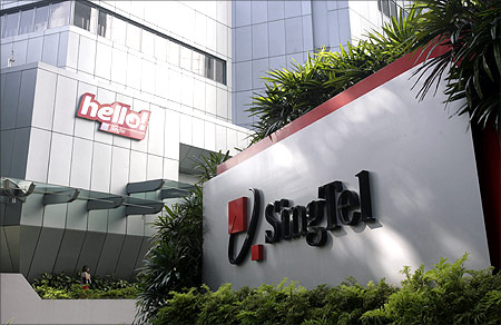A customer walks past Singtel logos after visiting a Hello shop at the company's headquarters in Singapore.