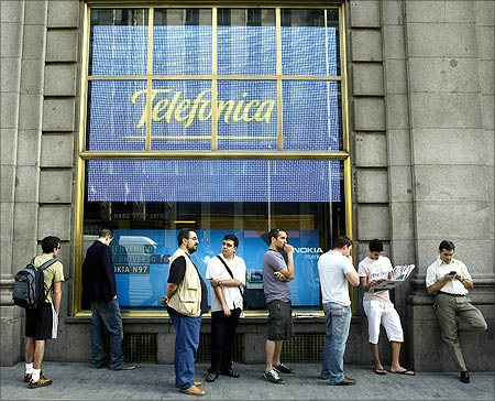 People wait in line to purchase the new iPhone 3GS on the first day it is being sold in Spain at a Telefonica store in Madrid.