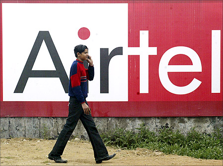 A boy talks on a mobile phone as he walks past a billboard of Bharti Airtel.