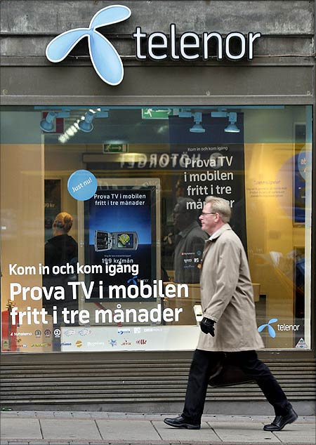 A pedestrian walks past a Telenor store in central Stockholm.