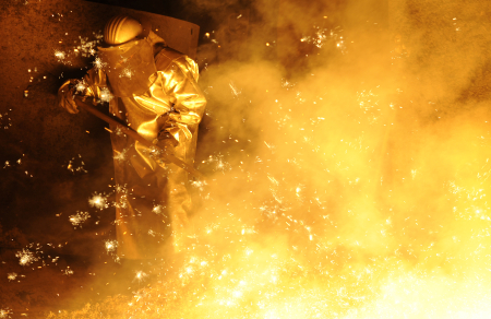 A steel-worker is pictured at a furnace at a plant.