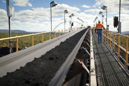 A man walks near a coal mine in Australia.
