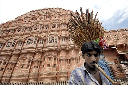 A vendor plays a flute as he tries to attract people to buy flutes in front of Hawa Mahal.