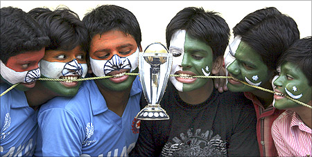 Cricket fans with their faces painted with the Indian and Pakistani national flags pose as they engage in a tug-of-war for a replica of the Cricket World Cup trophy in Hyderabad.