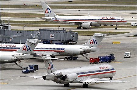 American Airlines planes sit at their gates.