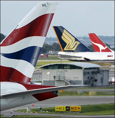 The tail wings of (L-R) British Airways, Singapore Airlines and Qantas Airways.