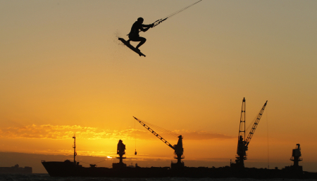 A kite surfer gets airborne in front of the stranded bulk carrier Seli 1 off Cape Town's Blouberg beach.