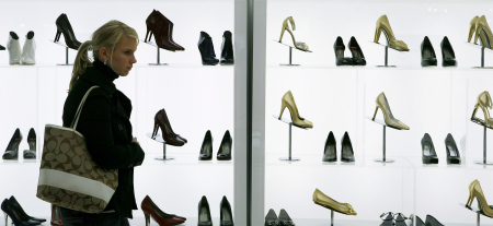 A woman looks at shoes while shopping in Macy's department store in New York City.