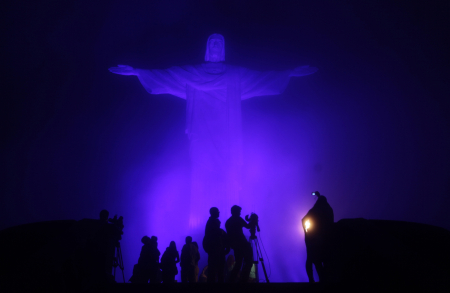People gather at the statue of Christ the Redeemer, lit by a blue light, on the eve of World Autism Day to commemorate the annual event in Rio de Janeiro.