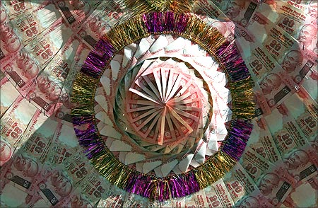 Indian currency notes are stapled to form a garland at a shop in Jammu.