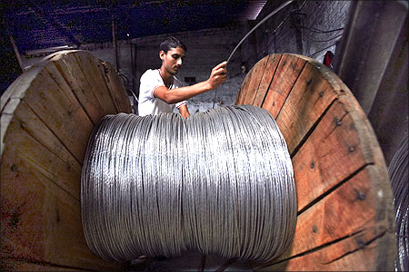 A man rolls electrical power lines onto a wooden wheel at a factory in the outskirts of Jammu.