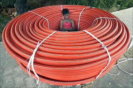A labourer sleeps in a roll of underground cables at a construction site in Jammu.
