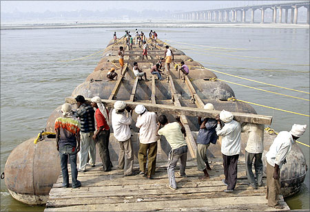 Labourers construct a temporary bridge made up of pontoons for Magh Mela festival on the river Ganges.