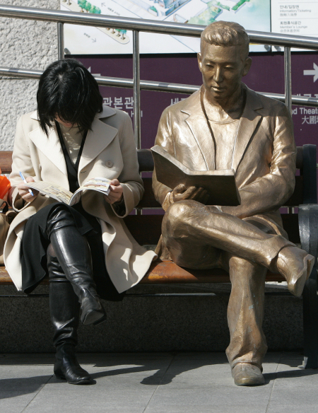 A woman reads a book beside a bronze statue in front of Sejong Centre for the Performing Arts in Seoul.