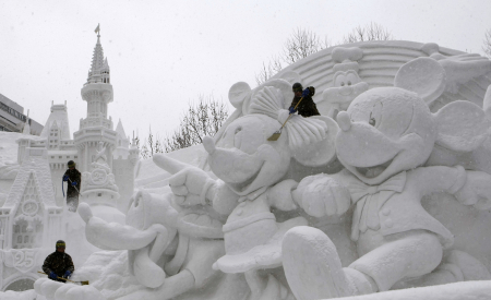 Japanese soldiers work on a snow sculpture celebrating the 25th anniversary of the Tokyo Disney Resort at the snow festival in Sapporo, Japan.