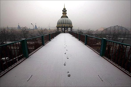 Footsteps in fresh snow are seen across a walkway.