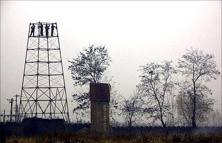 Farmers dismantle a tower in a field.
