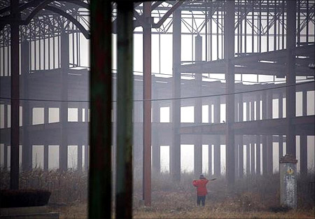 A farmer carries a shovel over his shoulder as he walks through an abandoned building, that was to be part of an amusement park called 'Wonderland', to tend his crops on the outskirts of Beijing.