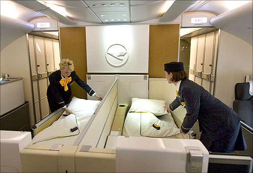 Flight attendants prepare beds of the First Class in a new Airbus A380 aircraft for Lufthansa.