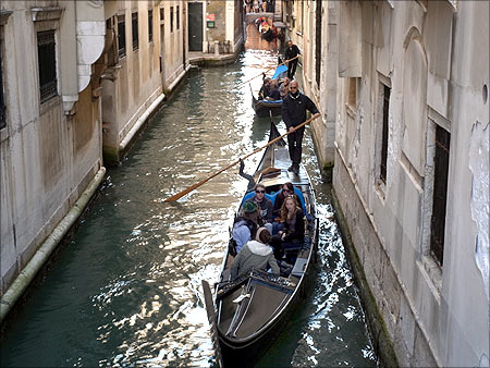 Gondolas make their way in a channel in downtown Venice.