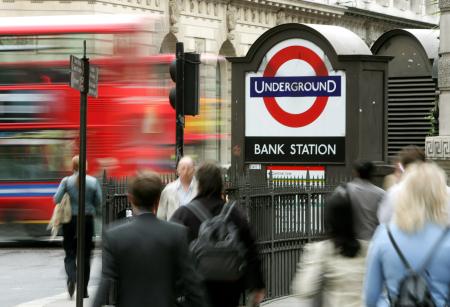 Pedestrians walk past an underground station in central London.