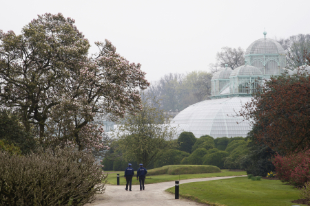 Police officers walk past greenhouses on the grounds of the Belgian royal family's residence of Laeken in Brussels.