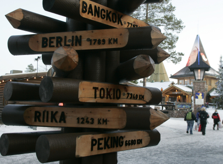 A signpost lists the distance to various cities from Santa Claus' Village at the Arctic Circle near Rovaniemi, Finland.