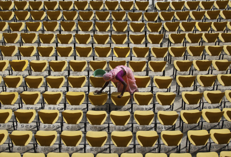 A worker cleans the seats of Vidarbha cricket association stadium in Nagpur.
