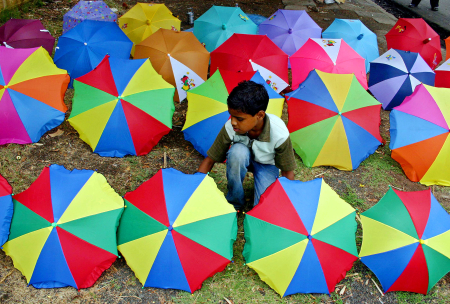 A boy prepares to sell his umbrellas in Bhopal.