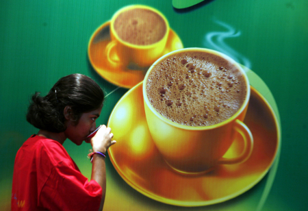 A visitor drinks coffee at the International Coffee Festival in Bangaluru.