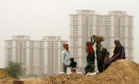 Labourers work in front of high rise residential colonies in Gurgaon.