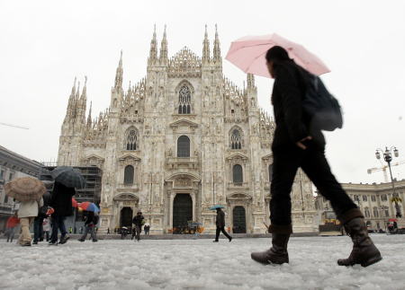 People walk past Duomo Cathedral after a snowfall in Milan.