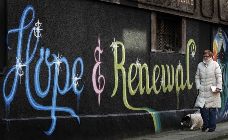 A woman walks past graffiti on the side of a building in Dublin.