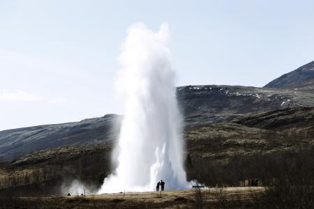 People look at a geyser in Geysir.