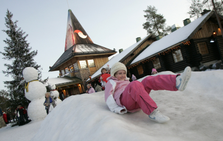 A child slides on snow in front of the Santa Claus' Office in Santa Claus' Village on the Arctic Circle near Rovaniemi, northern Finland.