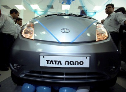 Visitors look at Tata Motors Nano car displayed at show room.