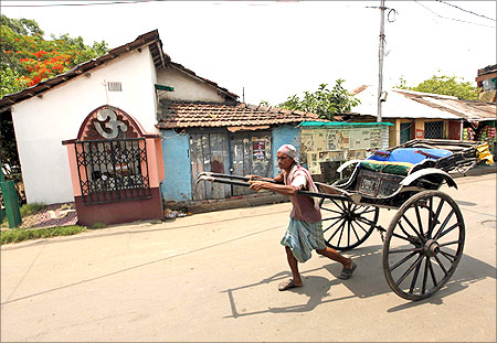 A handcart puller walks past the house of India's Railways Minister and Trinamool Congress (TMC) chief Mamata Banerjee in Kolkata.