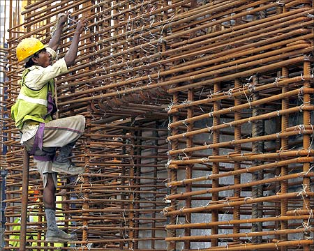 A worker climbs to fasten iron rods together at the construction site of a high-rise building in central Mumbai.