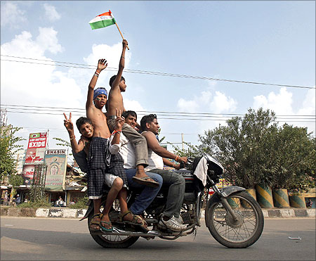 Supporters of veteran Indian social activist Anna Hazare ride on a motorcycle holding an Indian national flag.