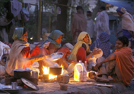 Homeless people prepare their food on a roadside near Ahemedabad.